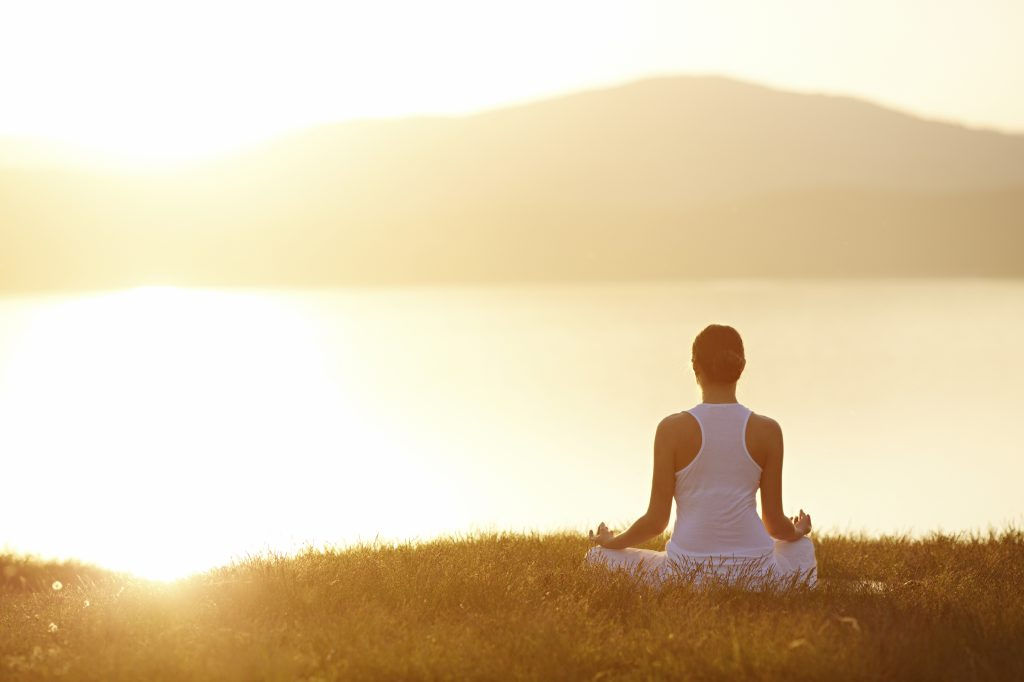 Woman sitting in lotus position on green grass in front of the mountains